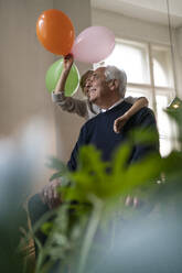Happy grandfather and grandson playing with balloons at home - GUSF02268
