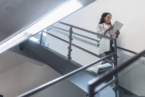 Low angle view of mixed race doctor reading medical chart on staircase - BLEF10397