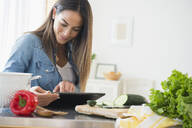 Caucasian woman using digital tablet for recipe - BLEF10439