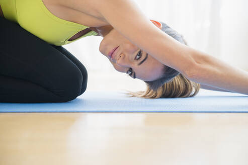 Caucasian woman stretching on yoga mat - BLEF10454