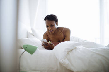 Woman lying in bed at home using cell phone - SODF00044