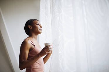 Woman at home looking out of window - SODF00050