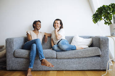 Two smiling women sitting on couch at home - SODF00053