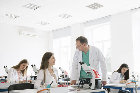 Lithuania, Vilnius, Students and teacher working in science class - AHSF00600