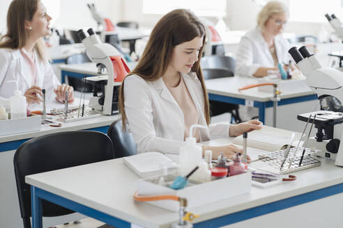 Lithuania, Vilnius, Young female researcher working in science class - AHSF00654