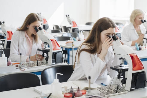 Researchers in white coats working with microscopes in lab - AHSF00657