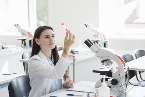 Lithuania, Vilnius, Young female researcher in white coat examining laboratory sample - AHSF00669