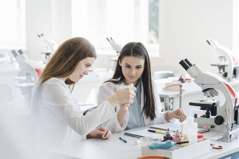 Young female researchers in white coats examining laboratory sample in science class - AHSF00672