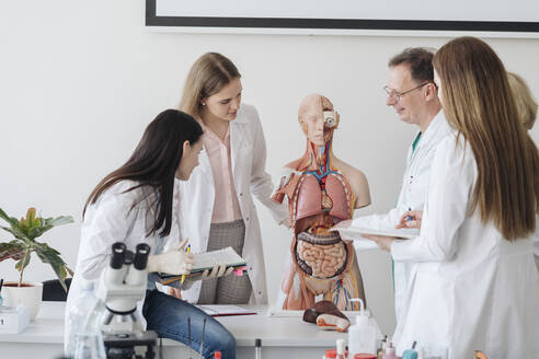Professor with students analyzing anatomy model in class - AHSF00684