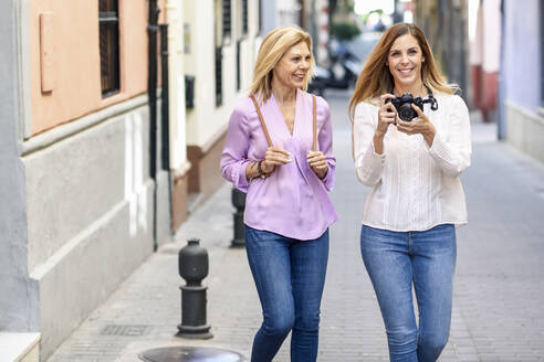 Mature woman traveling together with her daughter in the city - JSMF01179