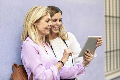 Smiling mature woman and her daughter using tablet together in the city - JSMF01182