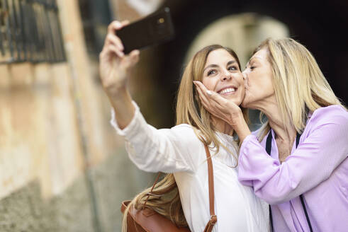 Happy woman taking a selfie with her mother in the city - JSMF01188