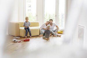 Happy family with two sons playing in living room of their new home - PESF01655