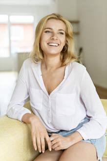 Deutschland, NRW, Köln, Portrat einer jungen Frau auf einem Sofa - PESF01673