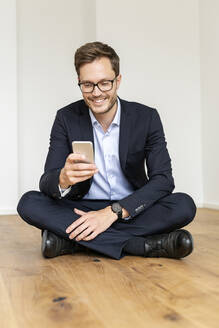 Smiling businessman sitting on the floor using cell phone - PESF01688