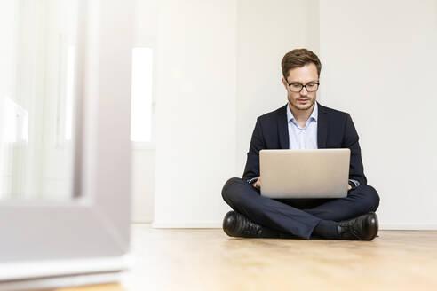 Businessman sitting on the floor using laptop - PESF01691