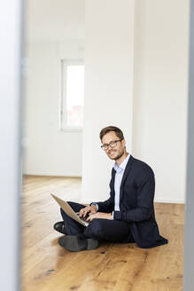 Portrait of a smiling businessman sitting on the floor using laptop - PESF01694