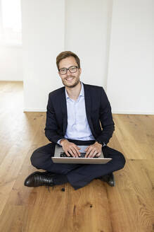 Portrait of a smiling businessman sitting on the floor using laptop - PESF01697