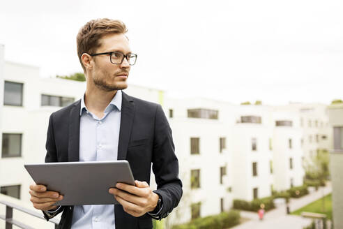 Businessman with tablet standing on balcony in a development area - PESF01700