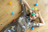 Laughing young woman lying on the floor with colourful balls - PESF01709