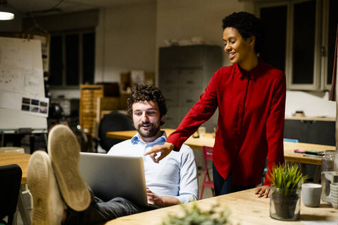 Businesswoman with businessman using laptop in office with feet on desk - GIOF06768