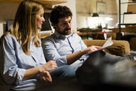 Businessman and businesswoman sitting on couch in office discussing papers - GIOF06810