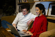 Businessman and businesswoman sitting on couch in office using laptop - GIOF06813