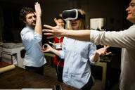 Colleagues with woman wearing VR glasses in office - GIOF06846