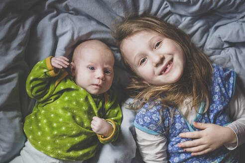 Portrait of smiling little girl lying on bed beside baby girl, top view - IHF00177