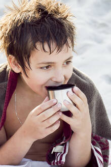 Portrait of boy warming himself up after swimming with a cup of tea - IHF00188