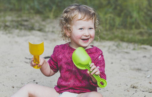 Portrait of happy toddler girl playing with sand - IHF00191