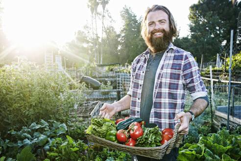 Caucasian man holding basket of vegetables in garden - BLEF10517