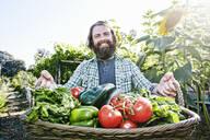 Caucasian man holding basket of vegetables in garden - BLEF10526