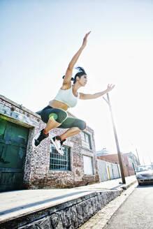 Mixed race woman jumping off sidewalk - BLEF10538