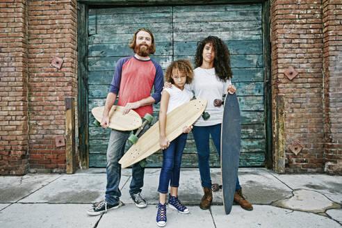 Family holding skateboards on sidewalk - BLEF10577