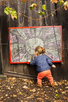 Caucasian baby girl drawing outdoors - BLEF10610