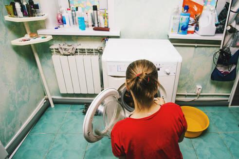 Caucasian woman loading laundry in dryer - BLEF10655