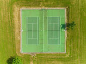 Aerial view of tennis courts surrounded by grass and trees. - AAEF00096