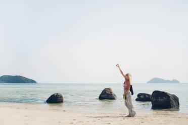 Caucasian woman taking selfie on beach - BLEF10698