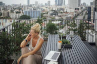 Caucasian woman talking on cell phone on balcony - BLEF10710
