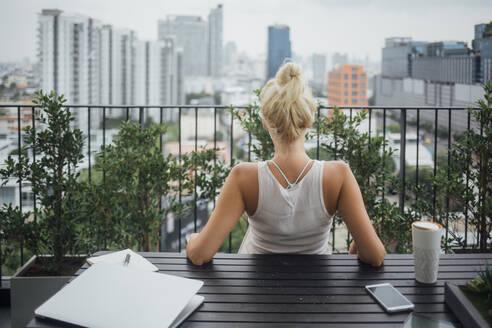 Caucasian woman sitting on balcony - BLEF10716