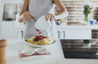 Caucasian woman pouring sauce on pasta in kitchen - BLEF10758
