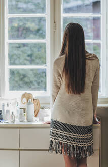 Caucasian woman looking out window - BLEF10779