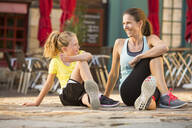 Caucasian mother and daughter stretching outdoors - BLEF10794