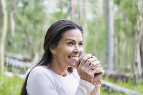 Hispanic woman having cup of coffee outdoors - BLEF10884