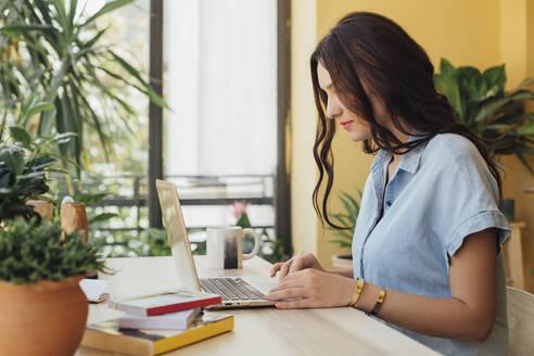 Caucasian woman using laptop at desk - BLEF10929