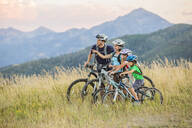 Caucasian family riding mountain bikes in field - BLEF10983