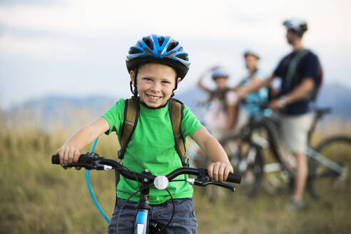 Caucasian boy smiling on mountain bike - BLEF10986