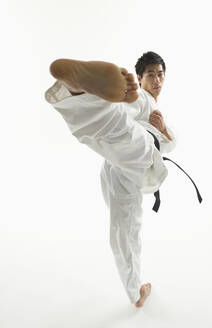 Asian male karate black belt kicking in air - BLEF11139