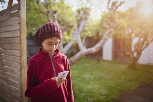 Mixed race girl using cell phone in backyard - BLEF11145